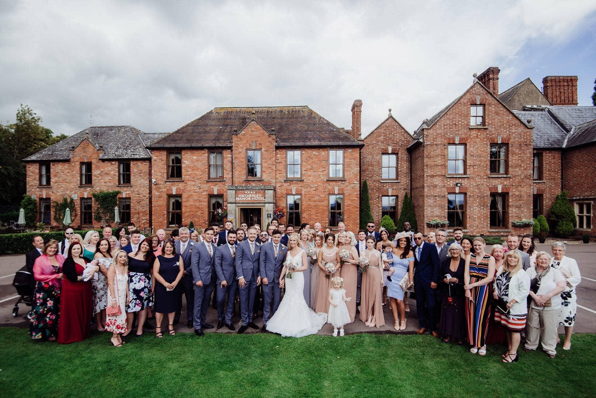 Hatherley Manor wedding photography of a large wedding group stood in front of the hotel