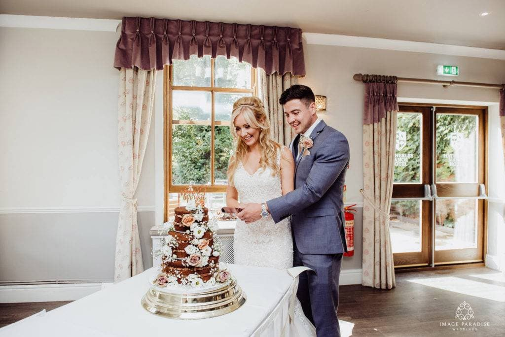 Newly married couple cut their wedding cake in the Mulberry suite