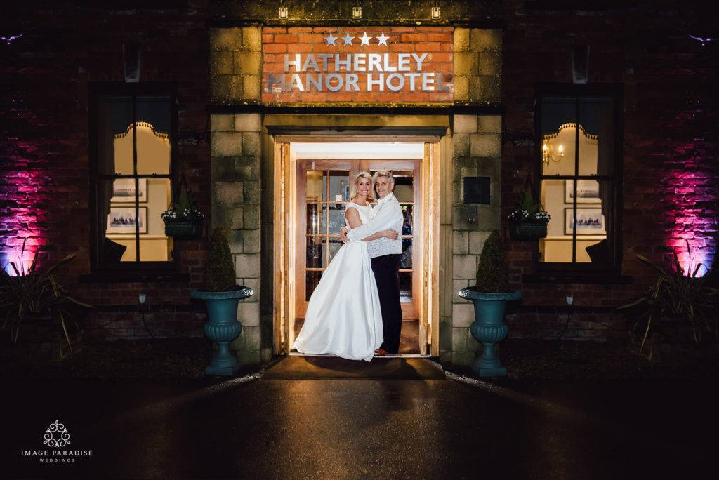 A night time portrait of bride and groom stood in the entrance of Hatherley Manor doorway with the sign above