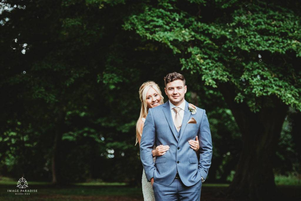 Couple stood in the grounds of Hatherley Manor Garden with trees in back ground