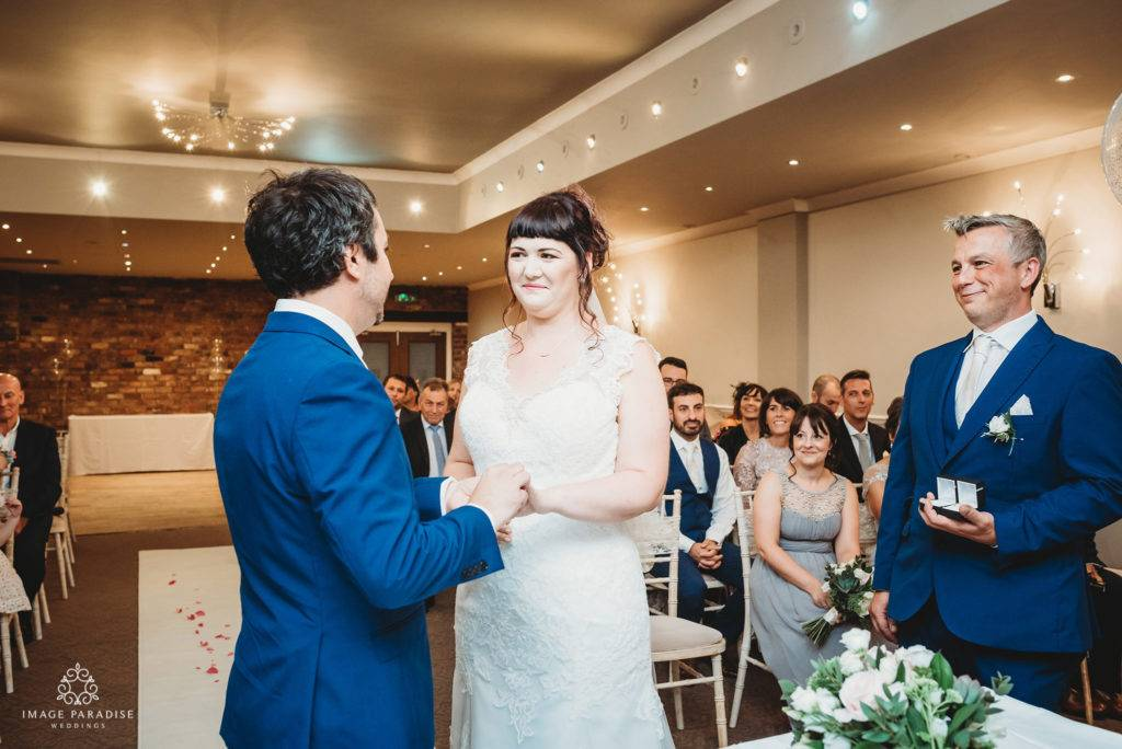 Bride and groom exchange rings in the moat suite at Hatherley manor wedding photography