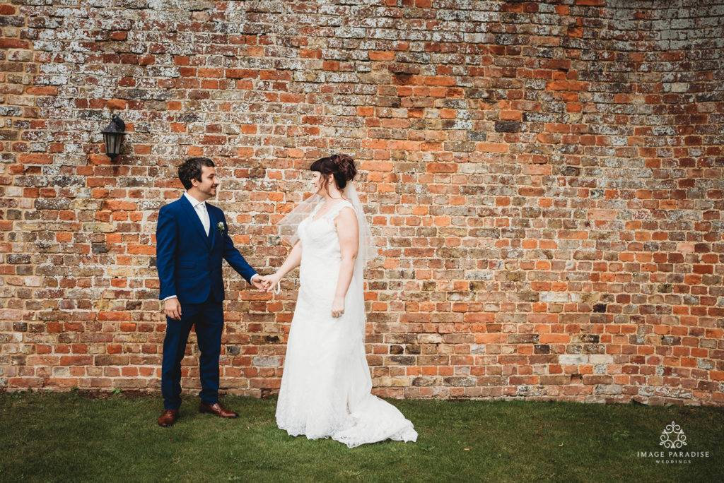 couple hold hands in front of the walled garden at Hatherley Manor