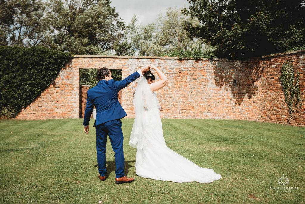 bride and groom dance in the walled garden of the moat suite Hatherley Manor wedding photography