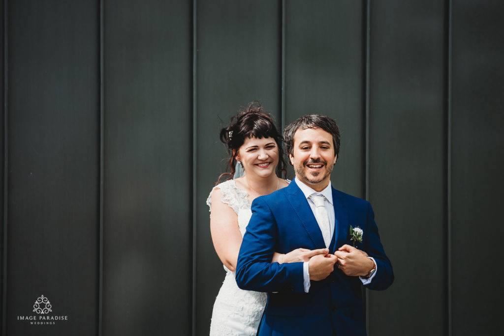Bride and Groom stood infront of dark panels.