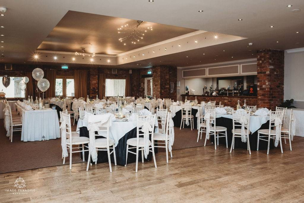 Tables and chairs laid out for a wedding breakfast in the Moat suite of Hatherley Manor
