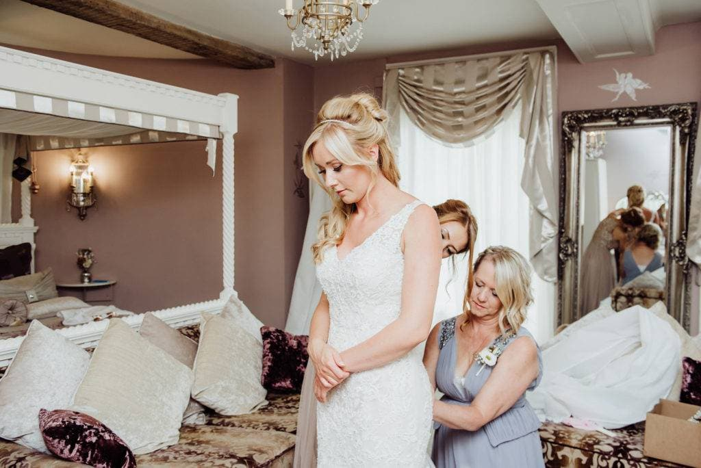 Bride being helped to do her wedding dress up in the bridal suite of Hatherley Manor