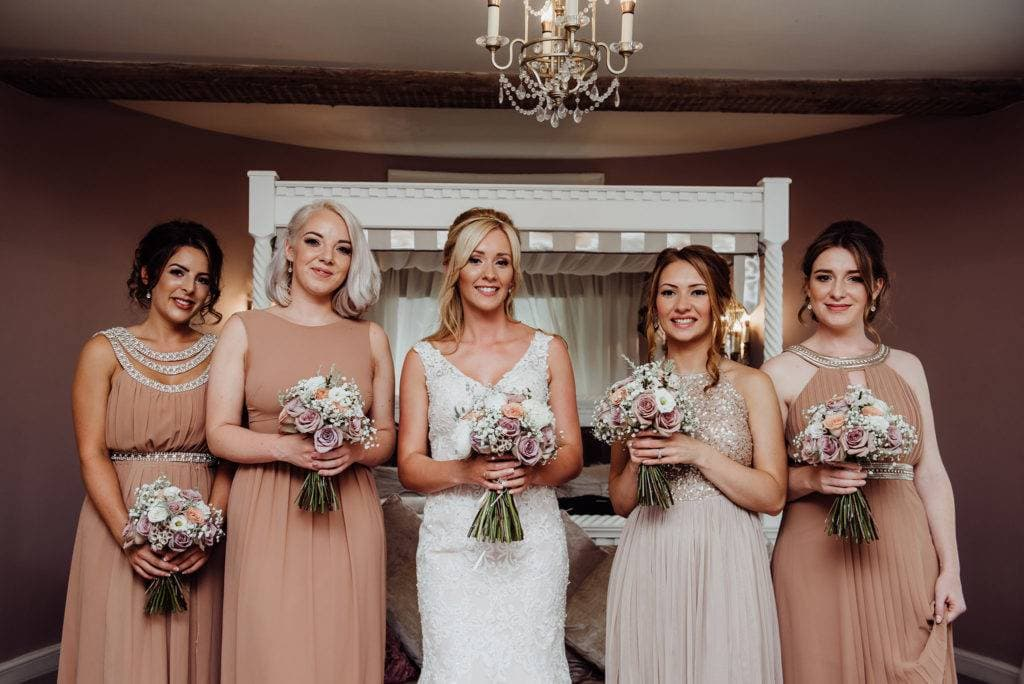 Bridesmaids stood holding flowers in the bridal suite at Hatherley Manor