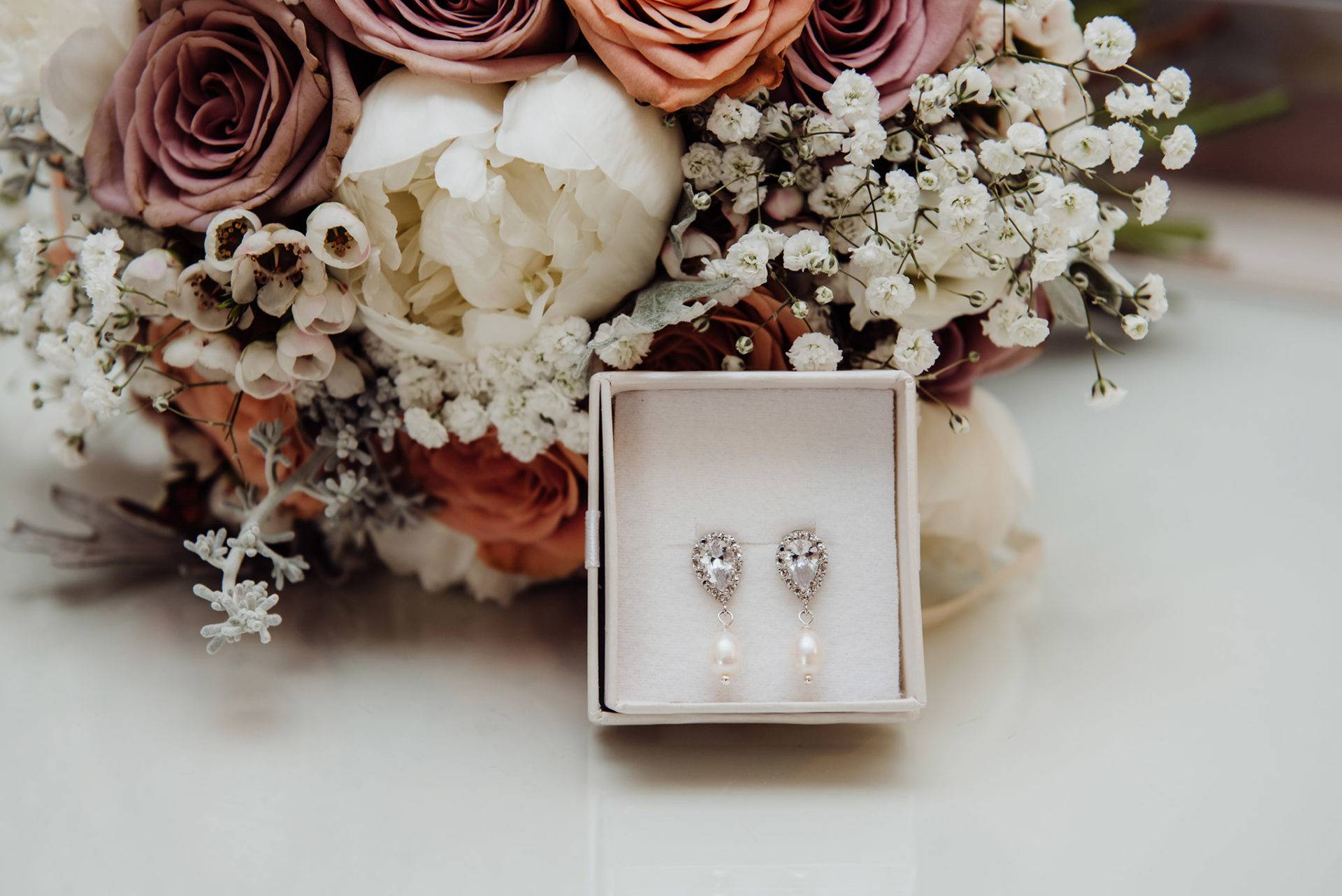 wedding earrings in front of flowers