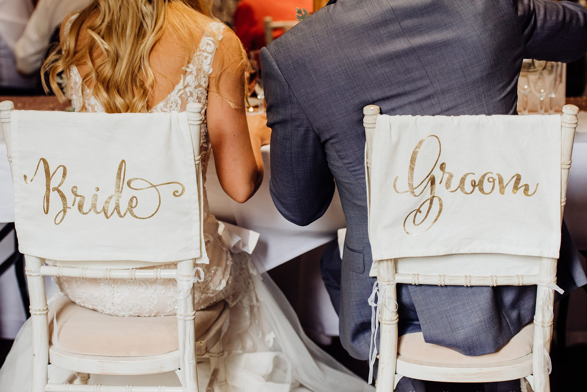 Bride and groom written on the back of chair covers