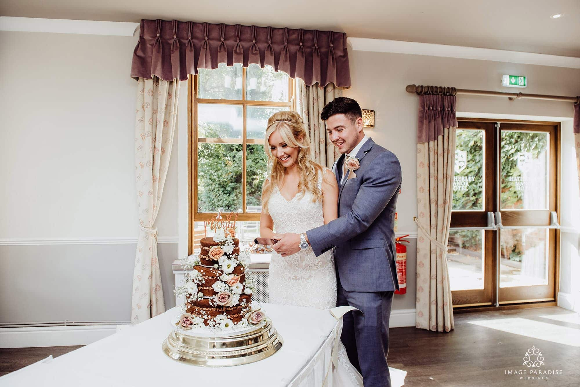 bride and groom cut cake at Hatherley Manor wedding venue