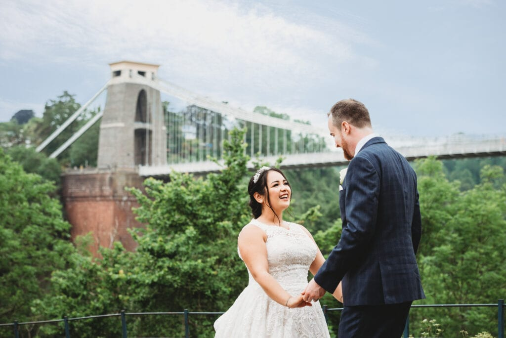 Bride and groom stood in front of the Clifton Suspension Bridge next to the Avon Gorge Hotel