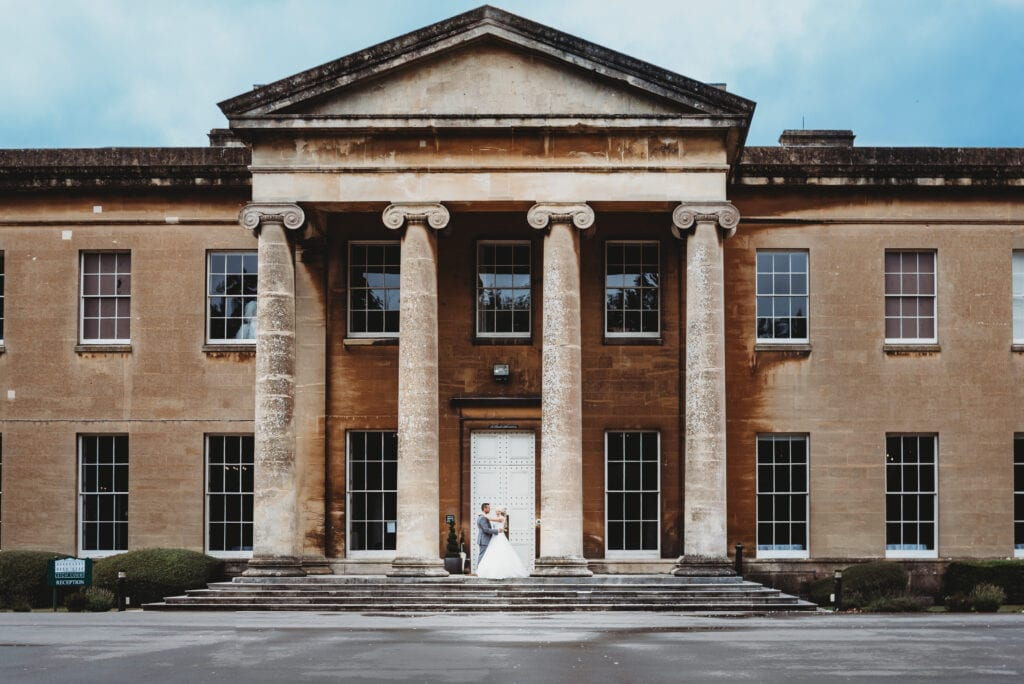 Couple stood between the columns at Leigh Court Bristol wedding venue