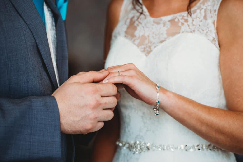Groom puts ring on brides hand at Walton Park