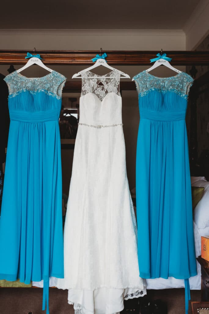 Brides wedding dress and bridesmaids outfits hang from a four poster bed at the Walton Park hotel.