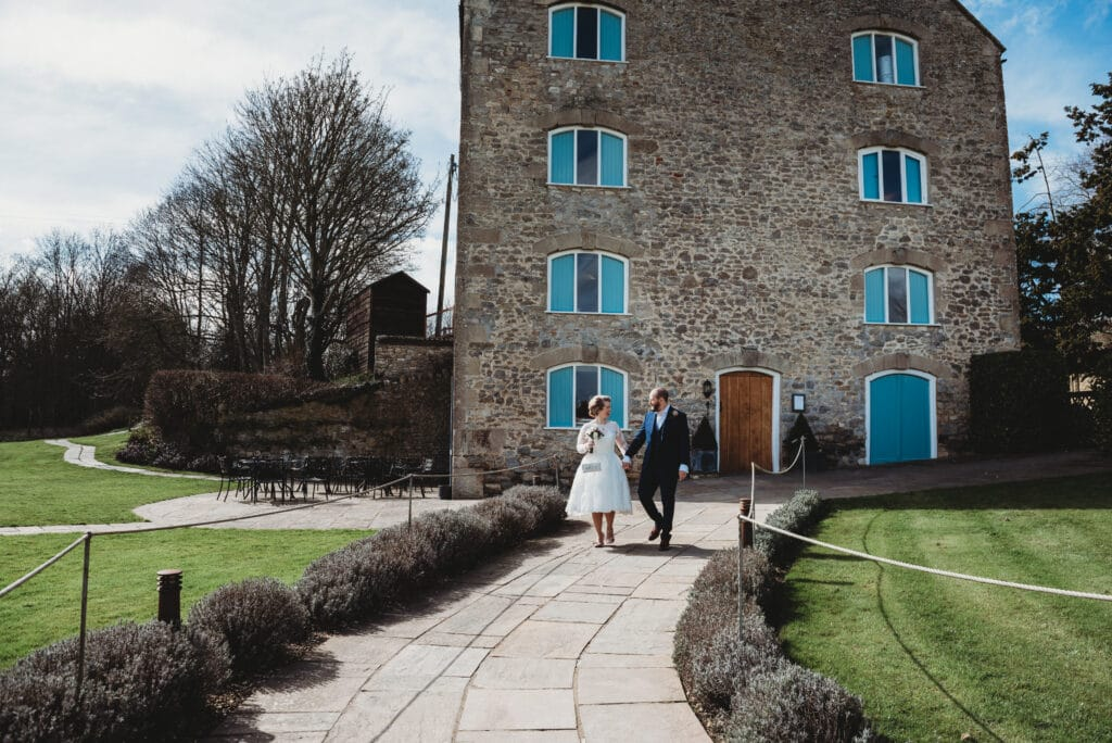 Couple walk down the path at Prison Mill wedding venue