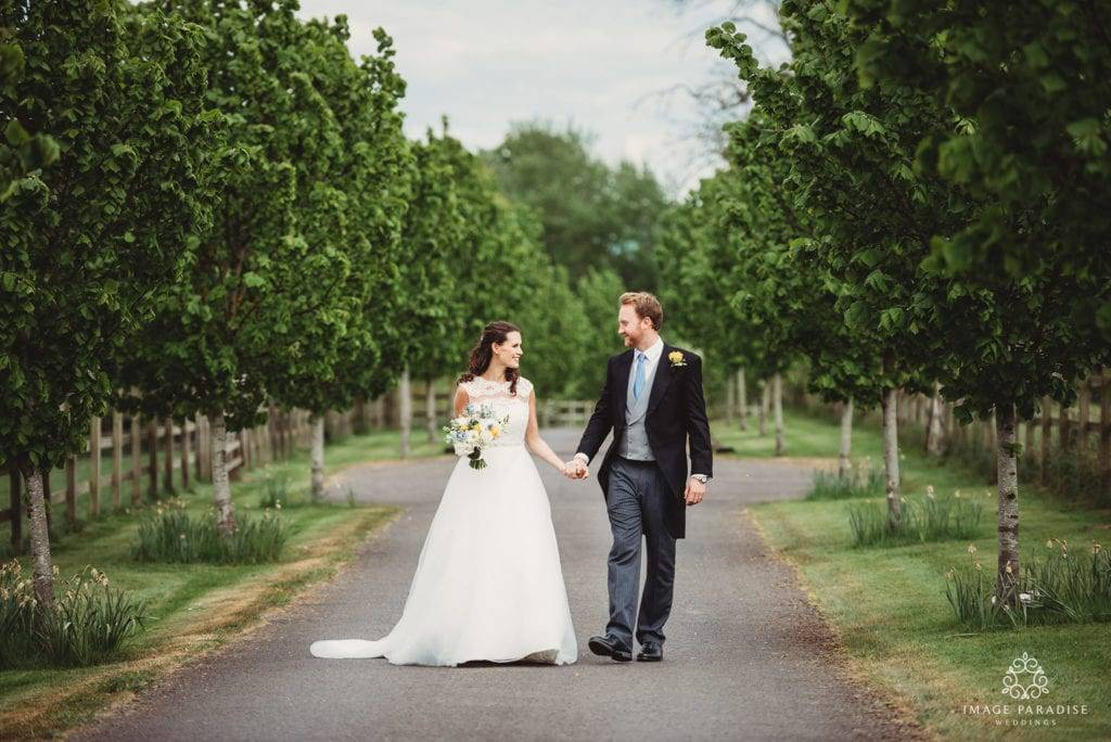 Bride and groom hold hands walking down the tree lined path of Wick Farm Bath wedding photographer
